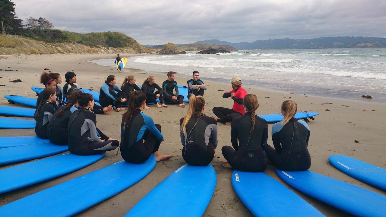 A group of students dressed in wetsuits sit in a circle on their surfboards on the beach listening to the instructor