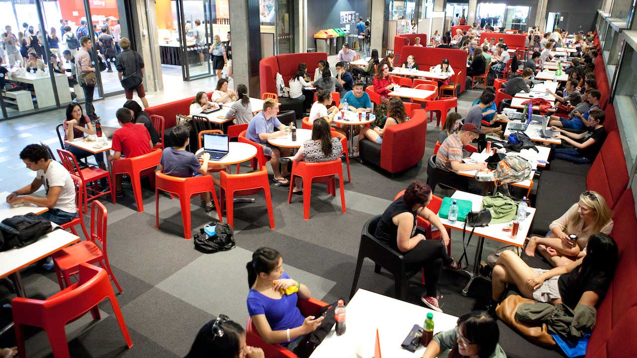 Students sit at tables in a dining hall on University of Canterbury's campus