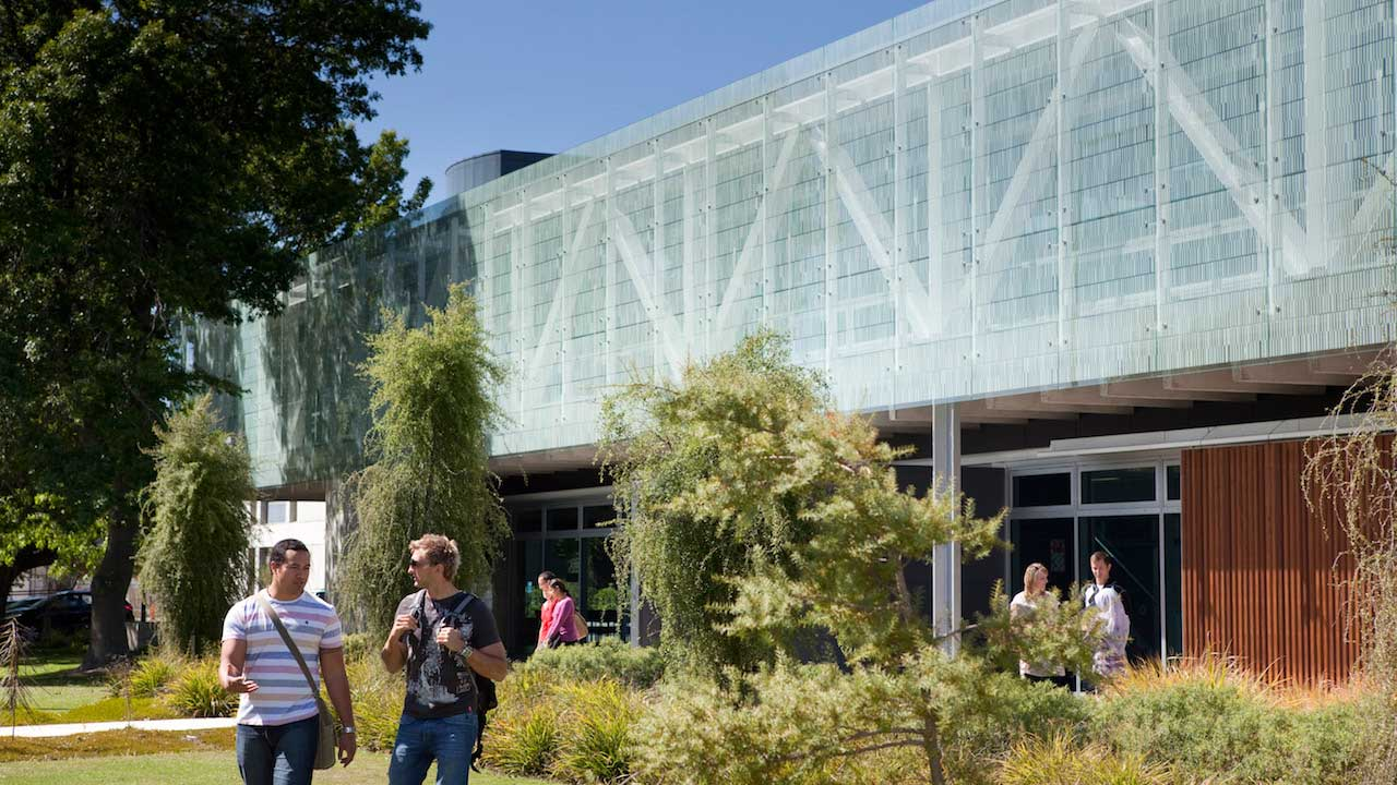 Two men converse and walk on University of Canterbury's campus