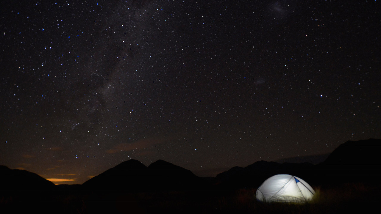 Stars shine bright across the dark sky and a tent stands illuminated in Arthur's Pass National Park, New Zealand
