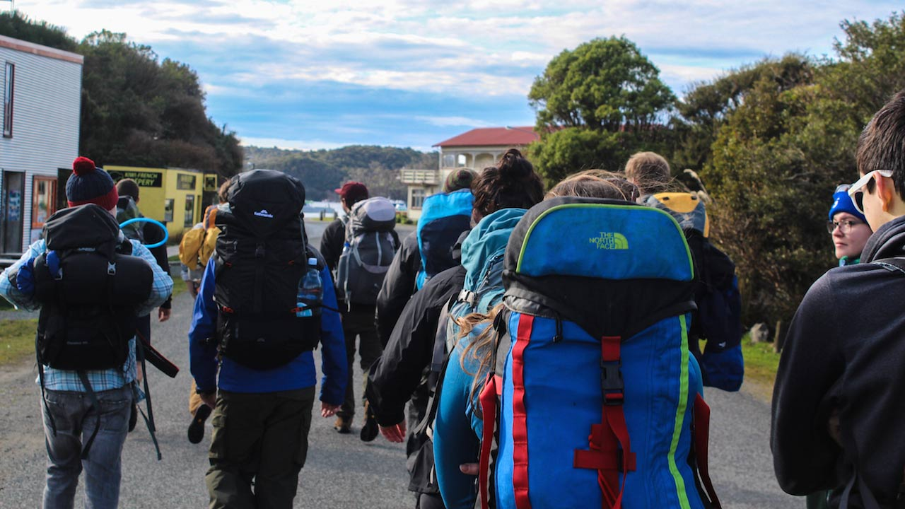A large group of people walking with backpacks in Dunedin, New Zealand
