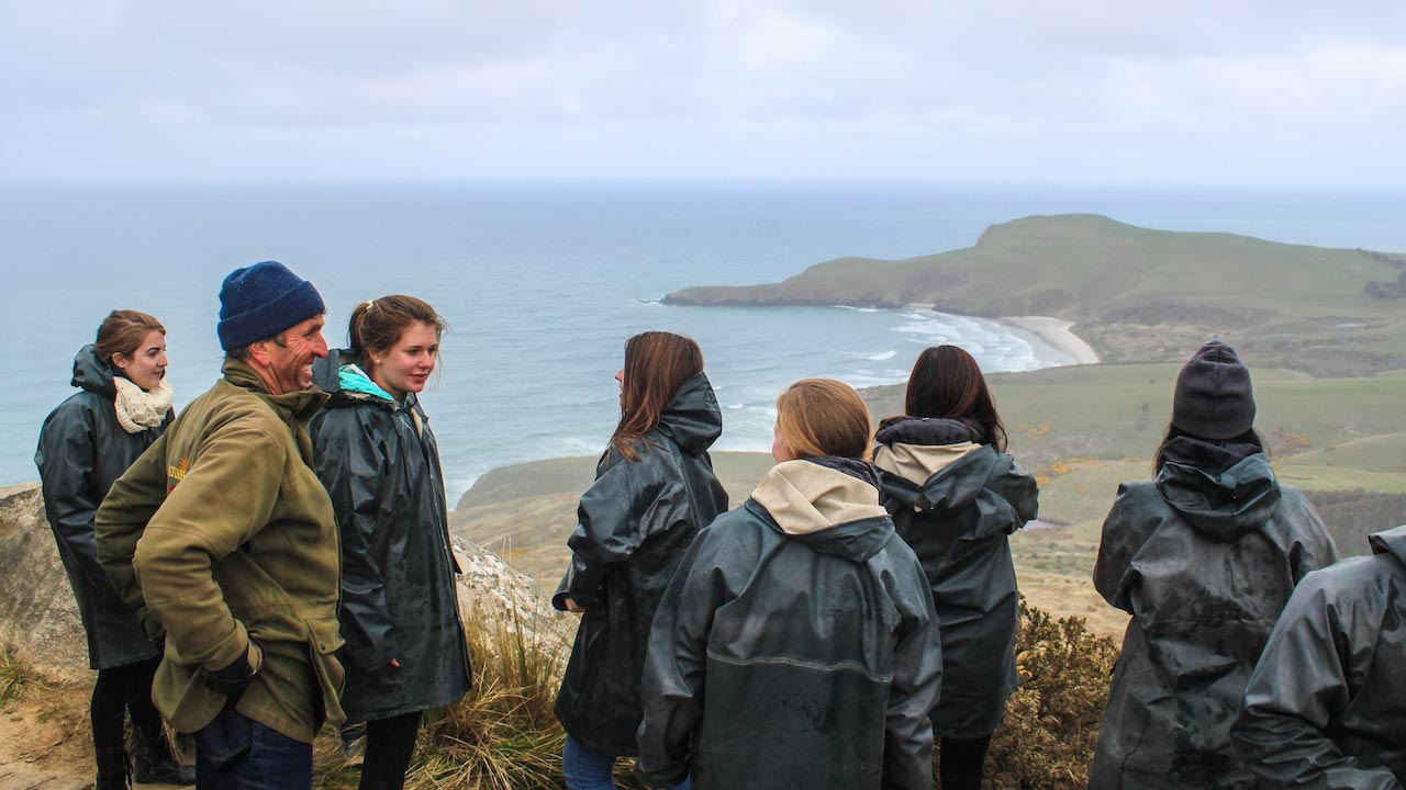 A group of people stand on a mountain top looking out over the ocean near Dunedin, New Zealand