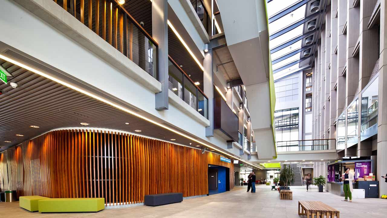 People walk along the bottom floor of a modern building on University of Auckland's campus