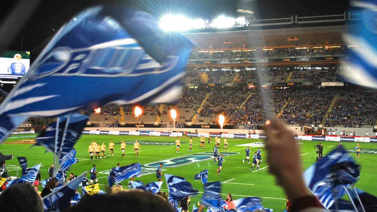 Fans wave flags as they watch a rugby match in Auckland
