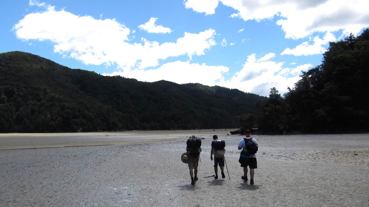 Three people walk with backpacks on flat ground towards the mountains near Wellington, New Zealand