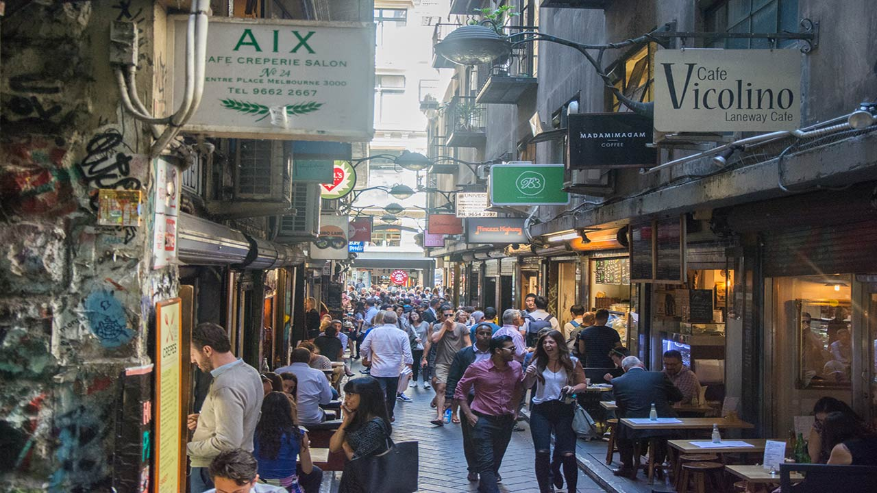 A crowded laneway lined with restaurants and shops in downtown Melbourne