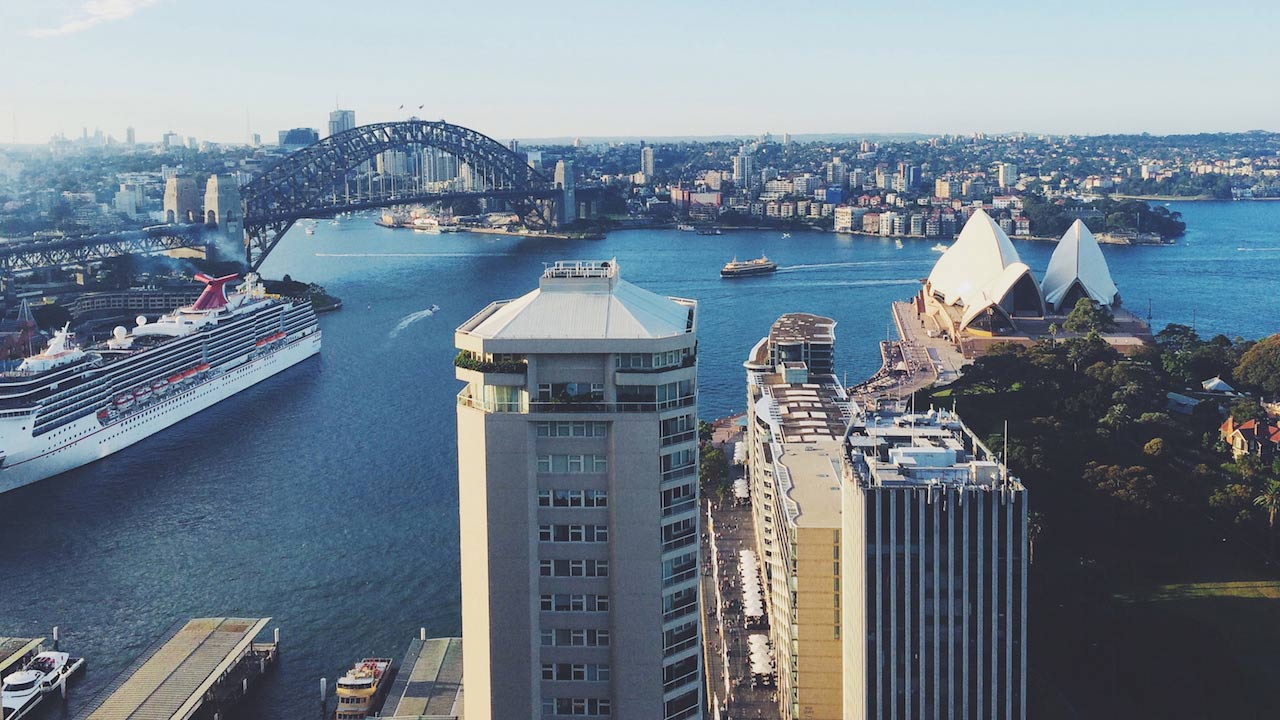 Sunny cityscape of Sydney, featuring the infamous Sydney Harbour Bridge and Sydney Opera House