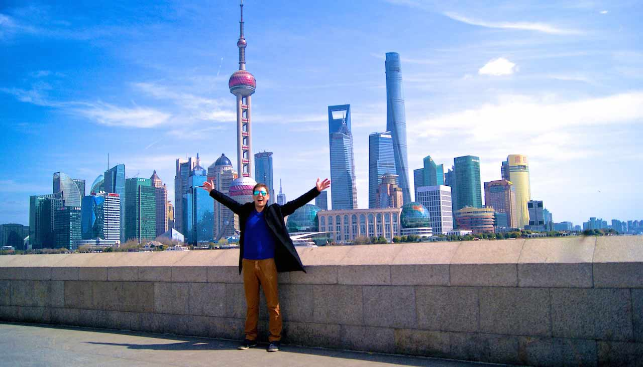 A man has his arms up in excitement while standing in front of the Shanghai cityscape