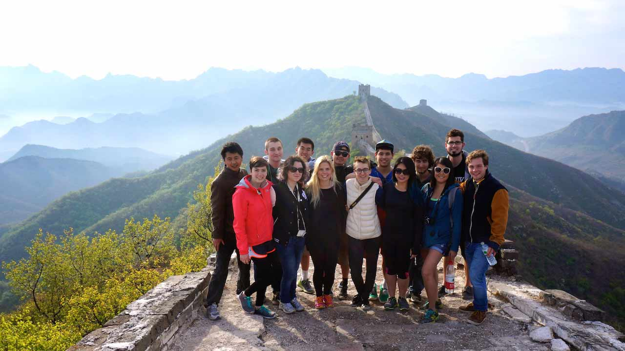 A group of students stand together smiling on the Great Wall of China