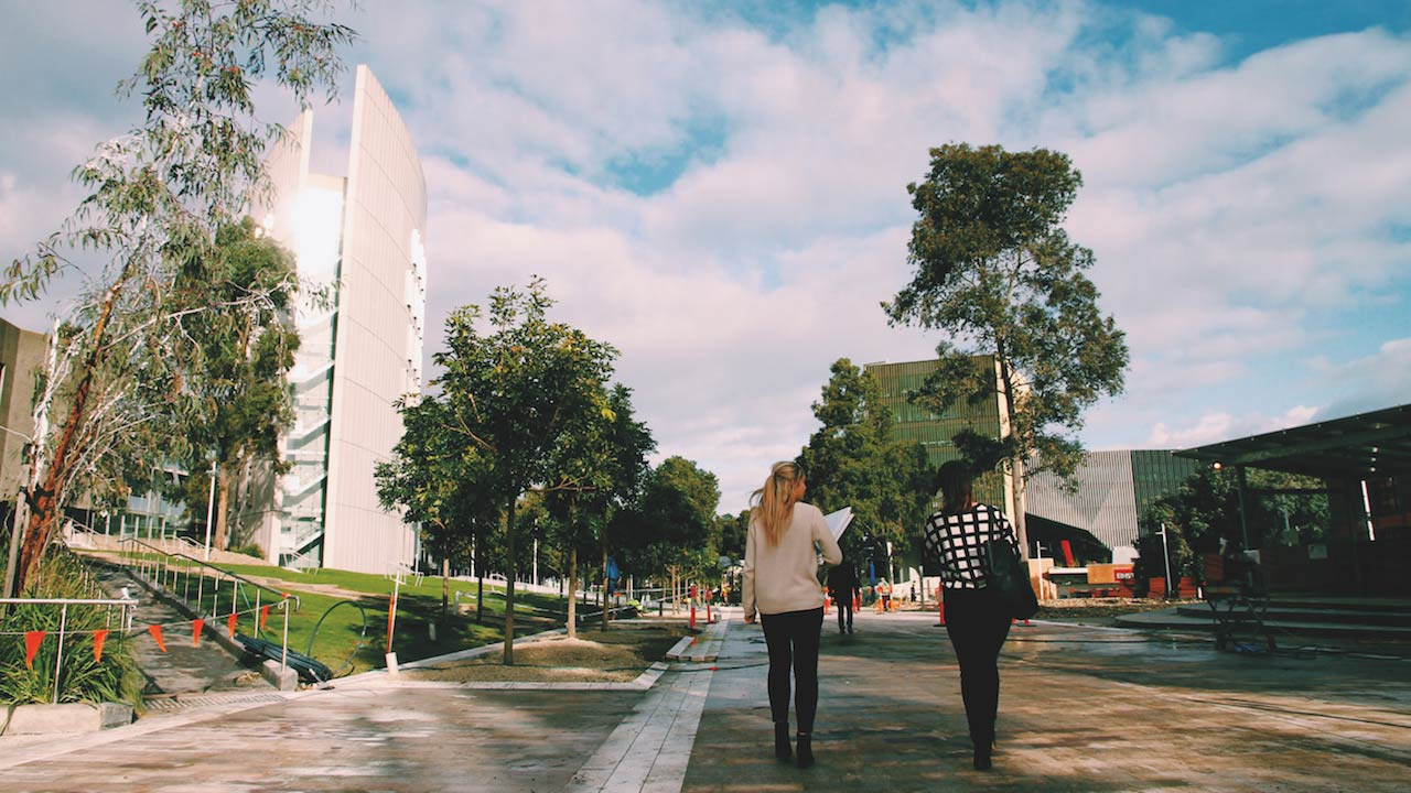 Two women walk along a pathway between buildings on Deakin's campus on a cloudy day