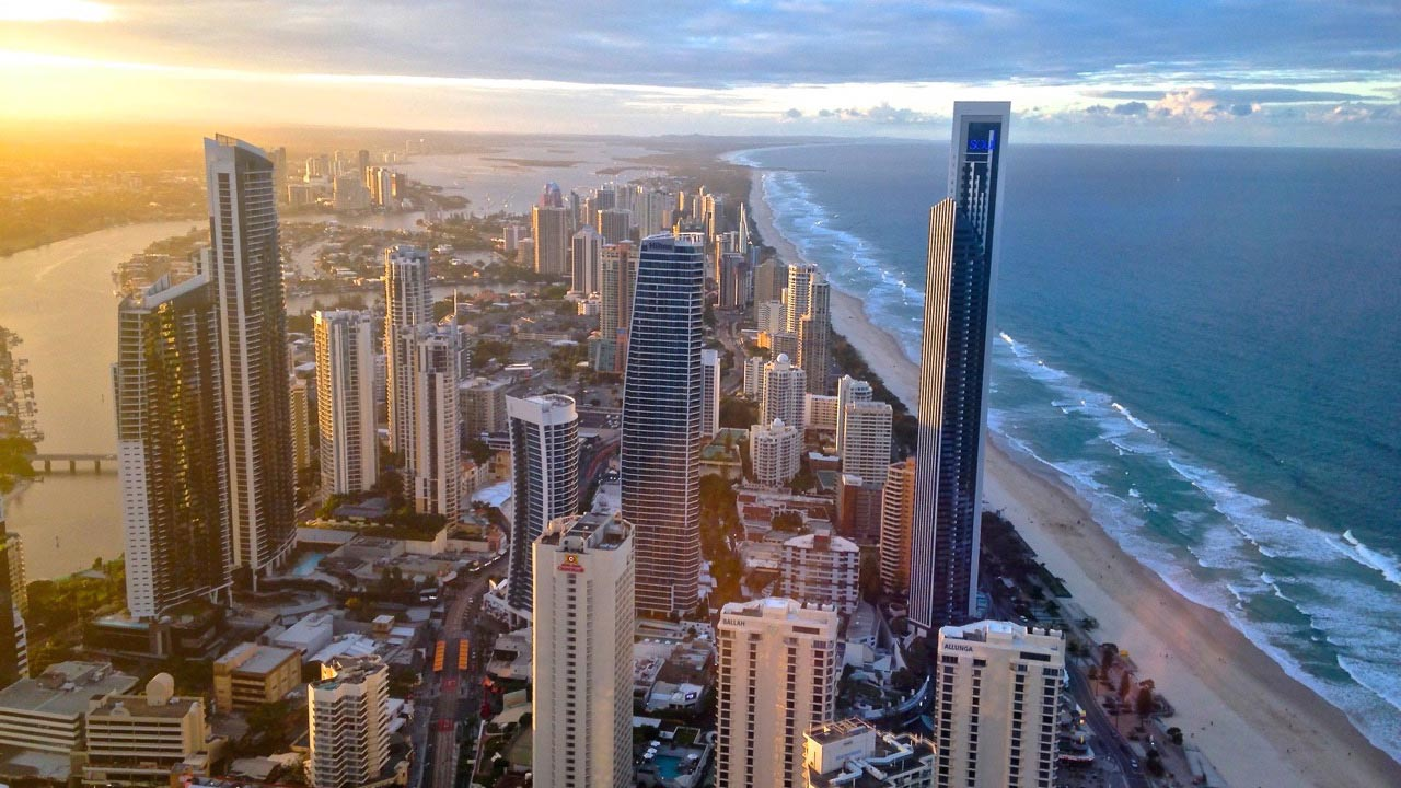 A bird's eye view of the Gold Coast's cityscape and coast as the sun sets