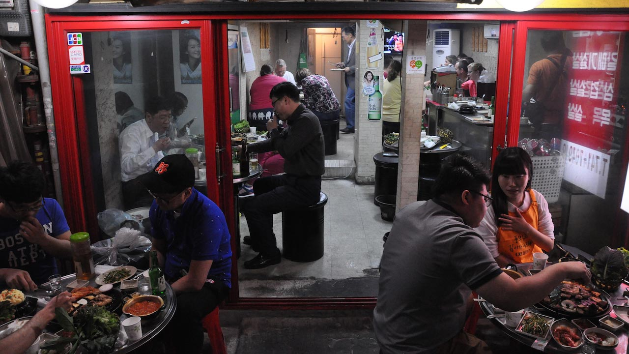 People sitting at tables in a hotpot restaurant in Korea