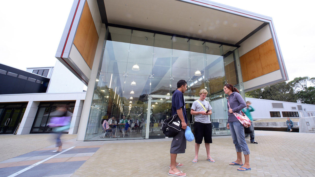 Three people stand outside a modern building on Massey University Palmerston North campus
