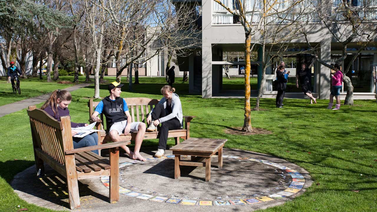 Three people sit on benches conversing outside on Massey University Palmerston North campus