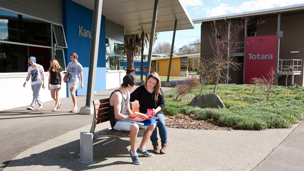 Two people sit conversing on a bench while others walk by on Massey University- Palmerston North campus