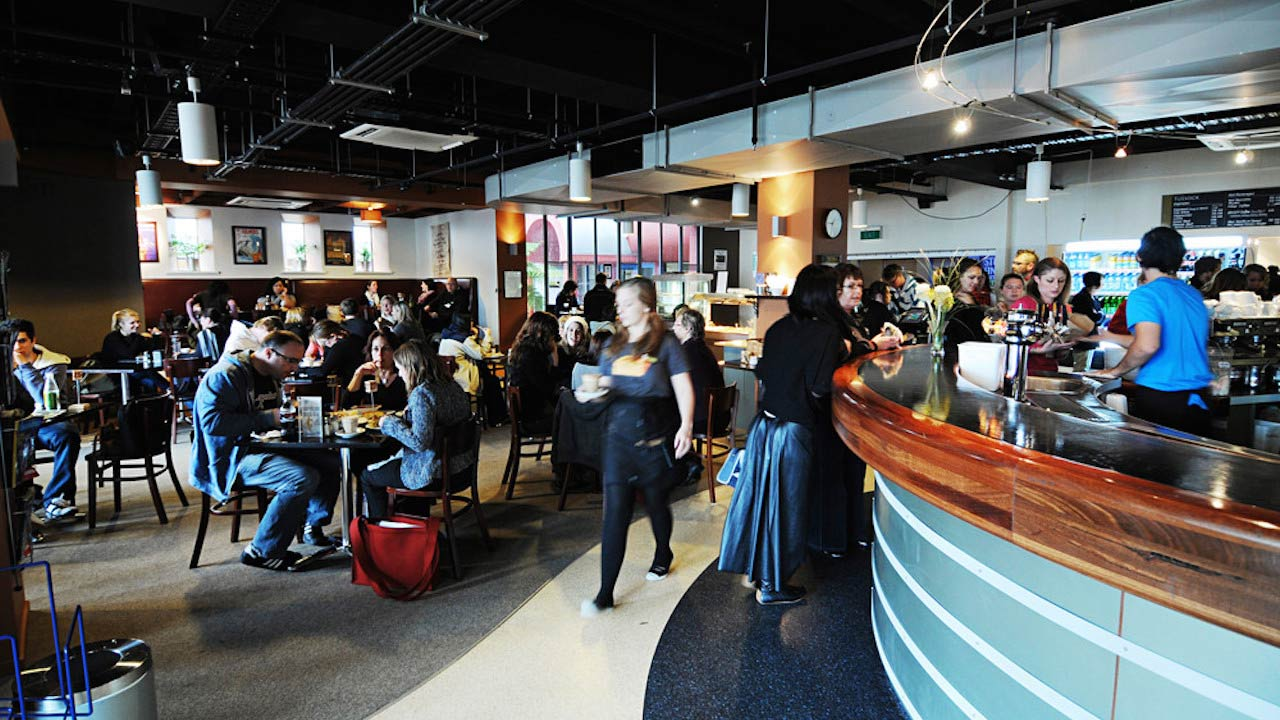 People sit at tables and order at an on-campus dining hub at Massey University Wellington
