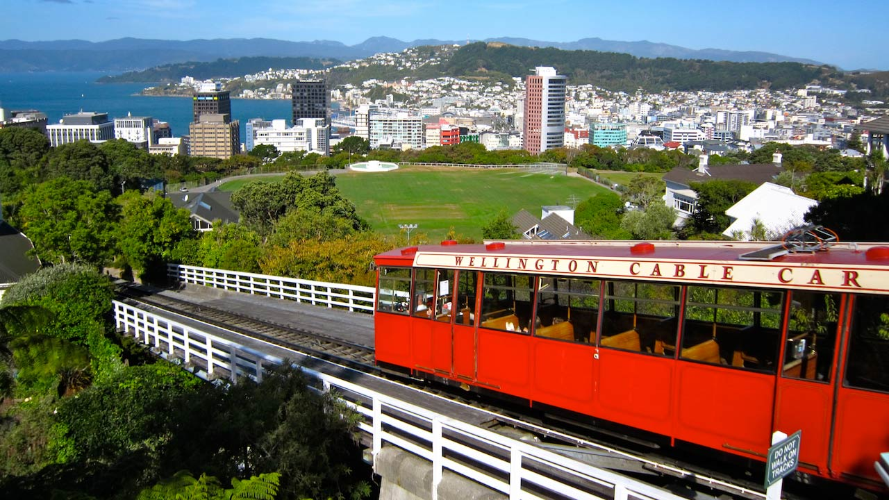 A red cable car traveling outside Wellington, New Zealand