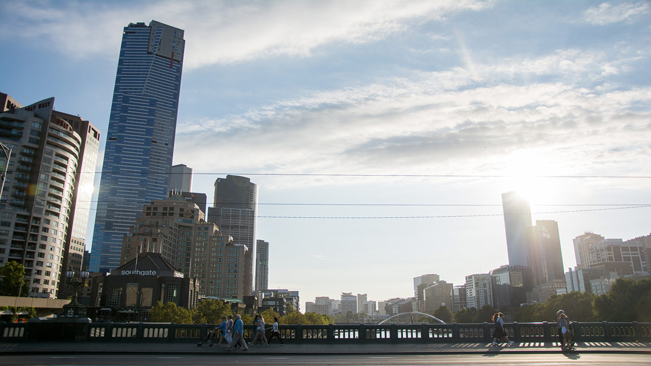 People walk along a bridge in downtown Melbourne that connects two city neighbourhoods at dusk
