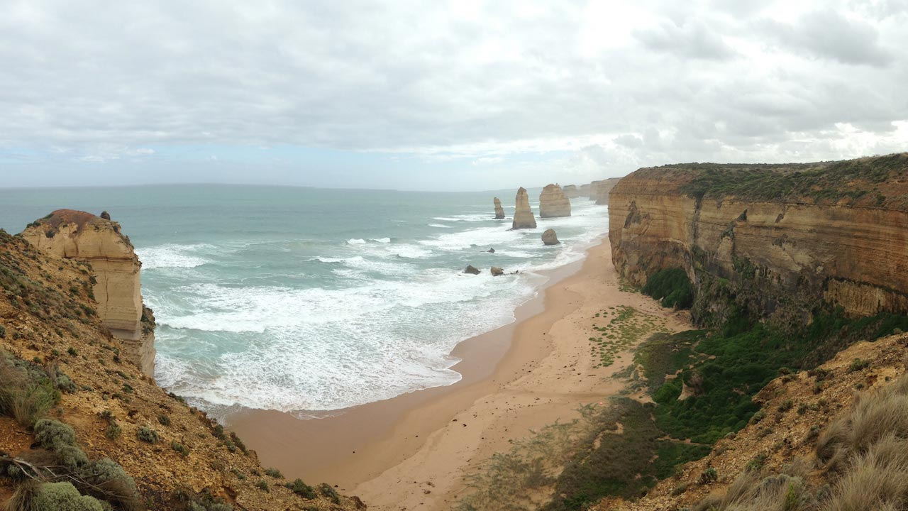 Limestone cliffs jutting out of the ocean as waves crash into the beach