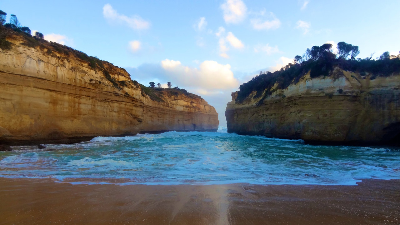 Waves crash onto the shore, set between two cliffs jutting from the ocean