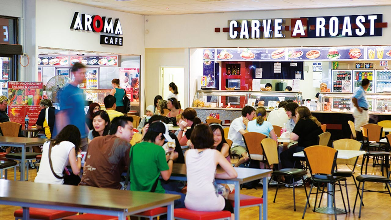 People sitting at tables in Murdoch University's student center in Perth, Australia
