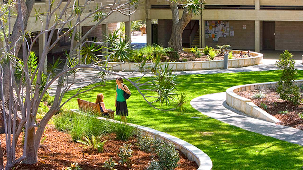 Two women chatting in a grassy quad on Murdoch University's campus in Perth, Australia