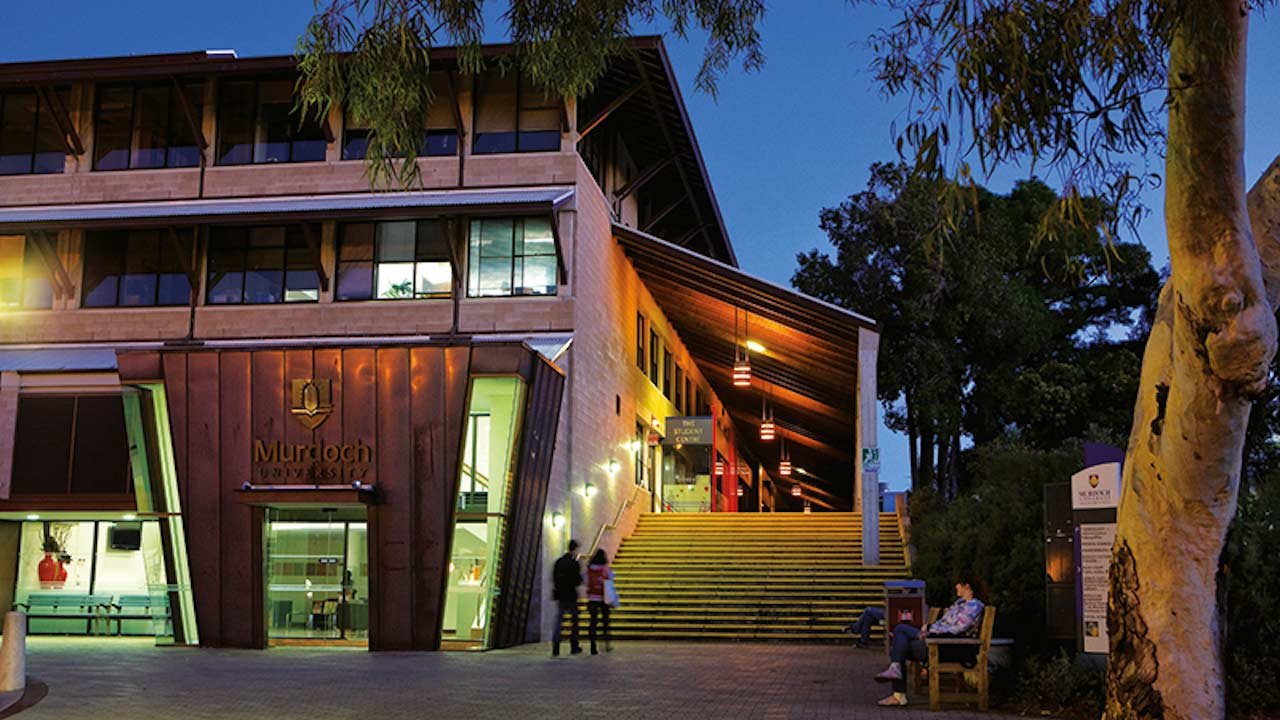 Two people walk towards an illuminated building on Murdoch University's campus in Perth, Australia
