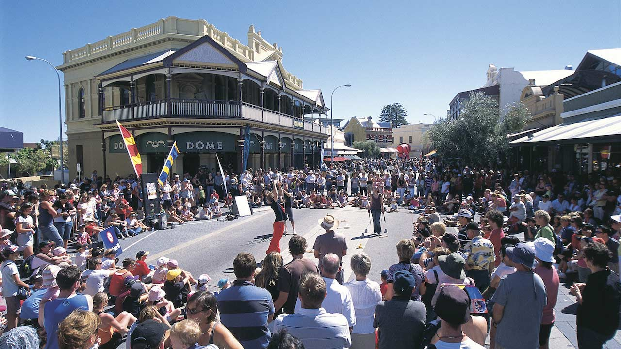 A crowd circles around street performers on the street in Perth, Australia