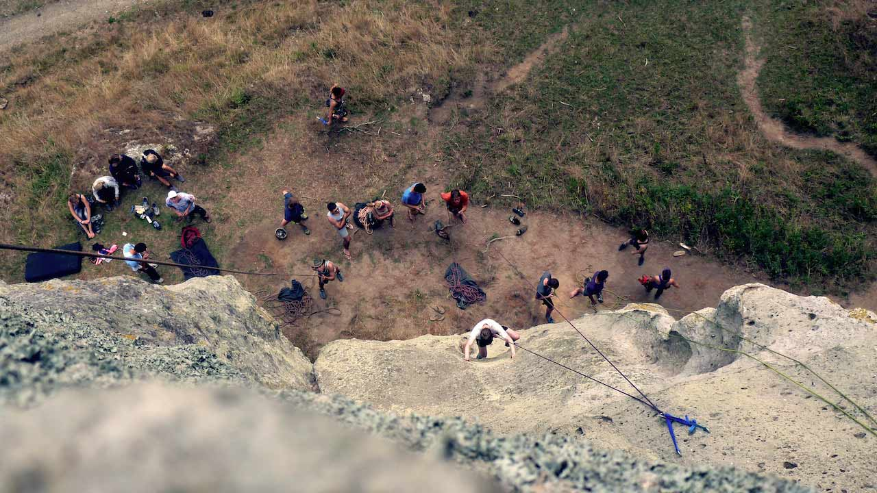 Students stand at the base of a craig as one person climbs up the rock formation