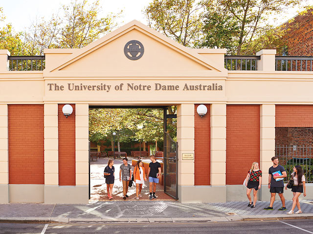 Two groups of students walk outside near the entrance of the University of Notre Dame Australia in Perth
