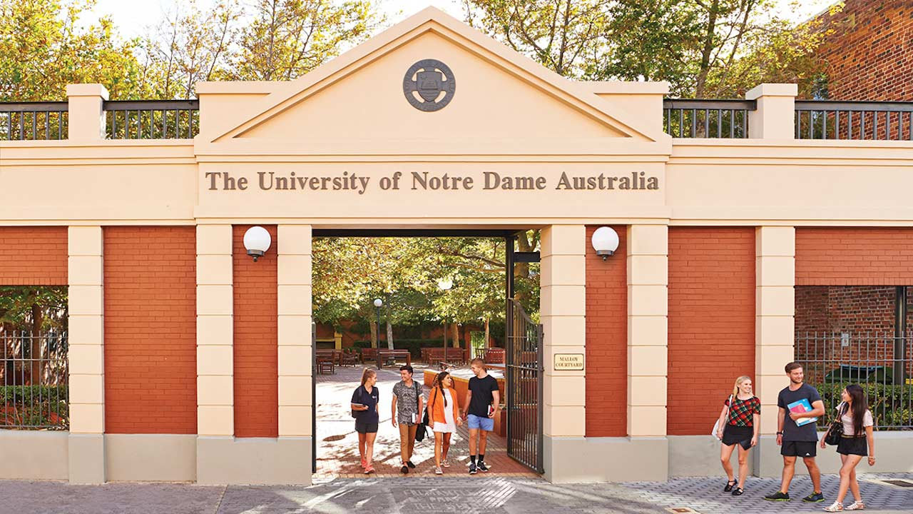Two groups of students walk outside below the entrance of the University of Notre Dame Australia in Perth