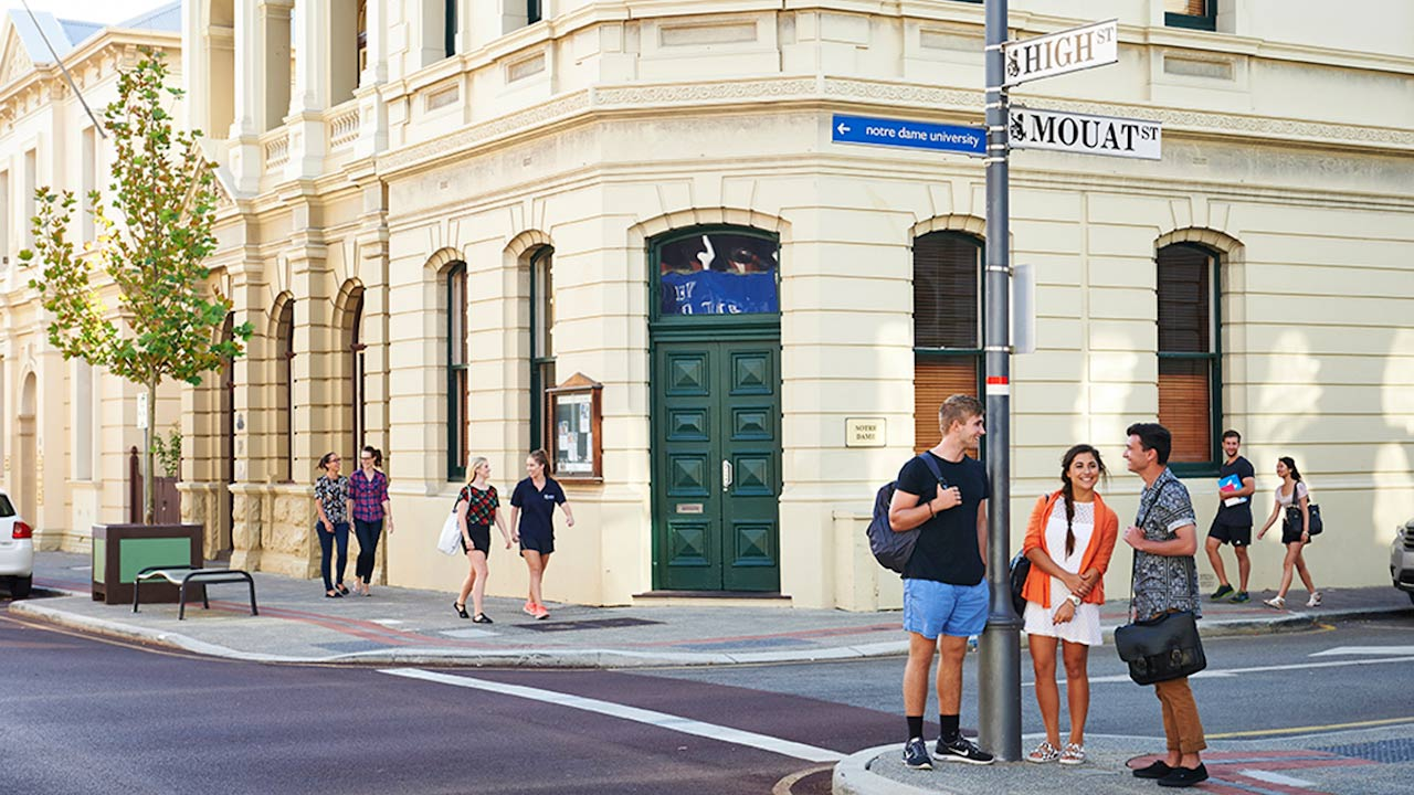 Two men and a woman stand conversing at a street corner in Perth, Australia