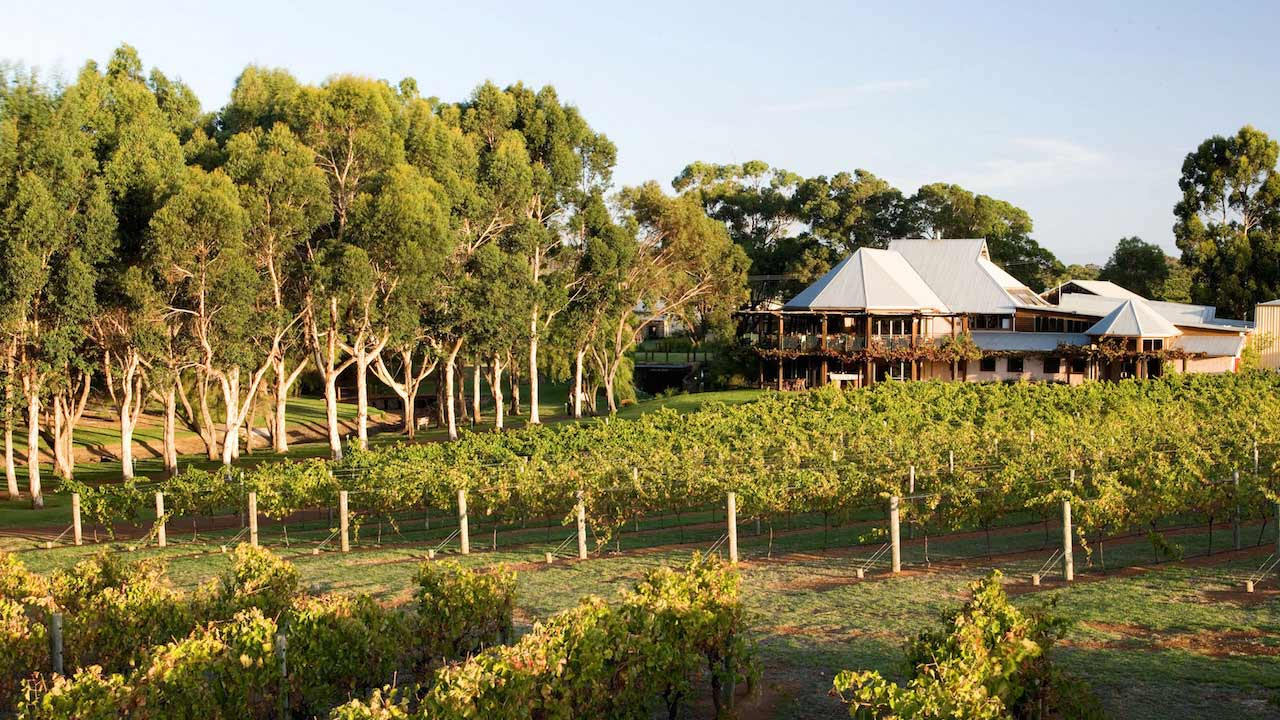 A beautiful house stands behind a large plot of farming during the golden hour near Perth, Australia