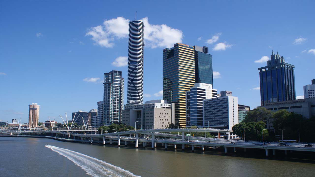 A boat cruises down the Brisbane River beside a business district