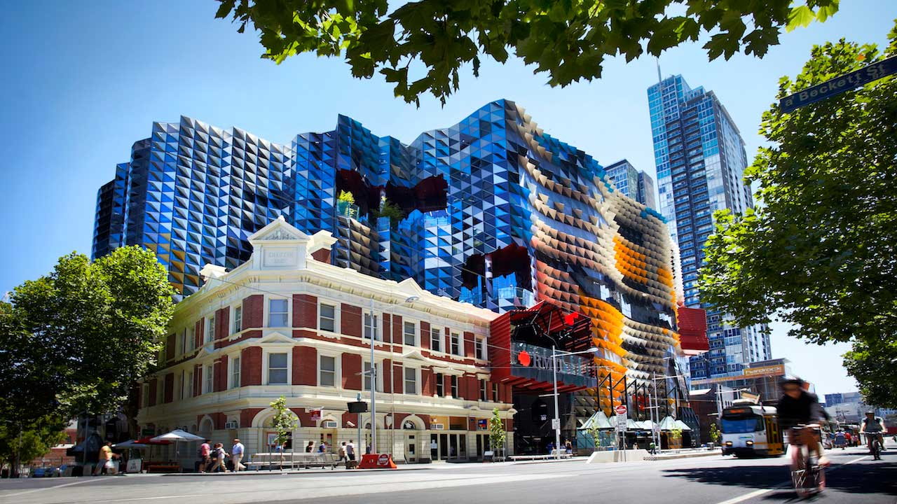 A biker riding past a corner of Melbourne that's home to RMIT's urban campus