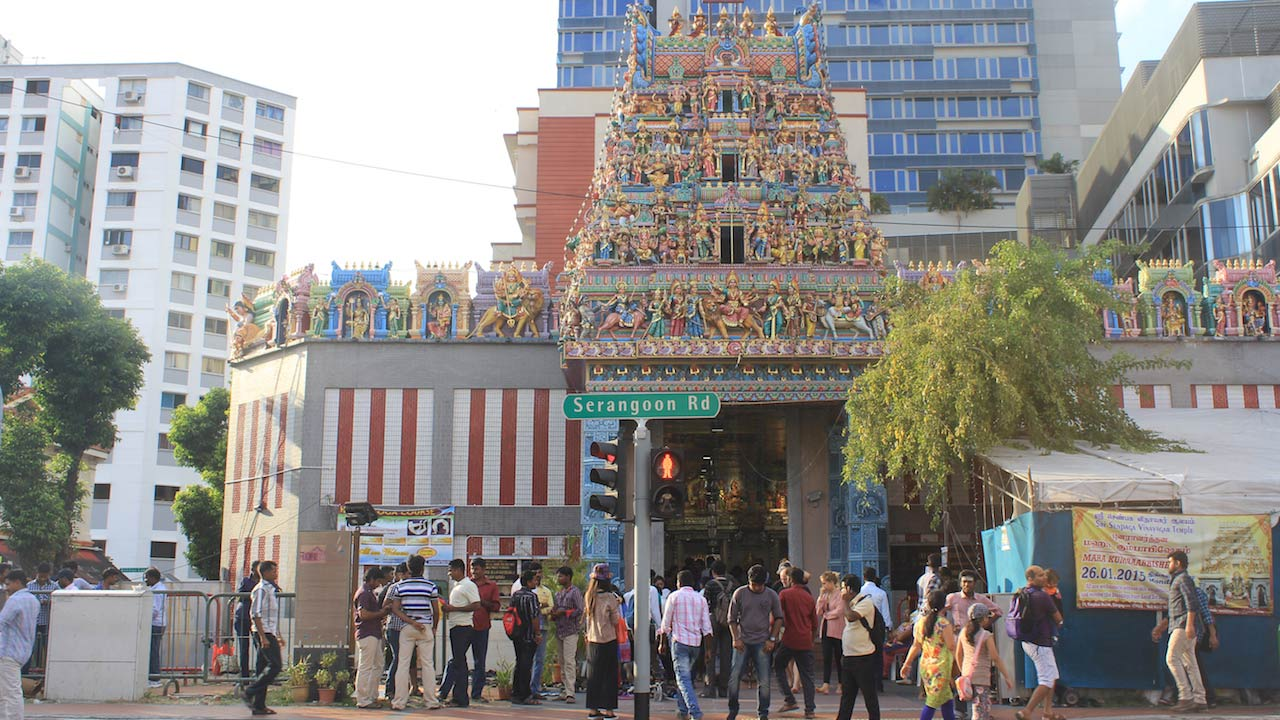 Crowds of people walking near a temple in Singapore