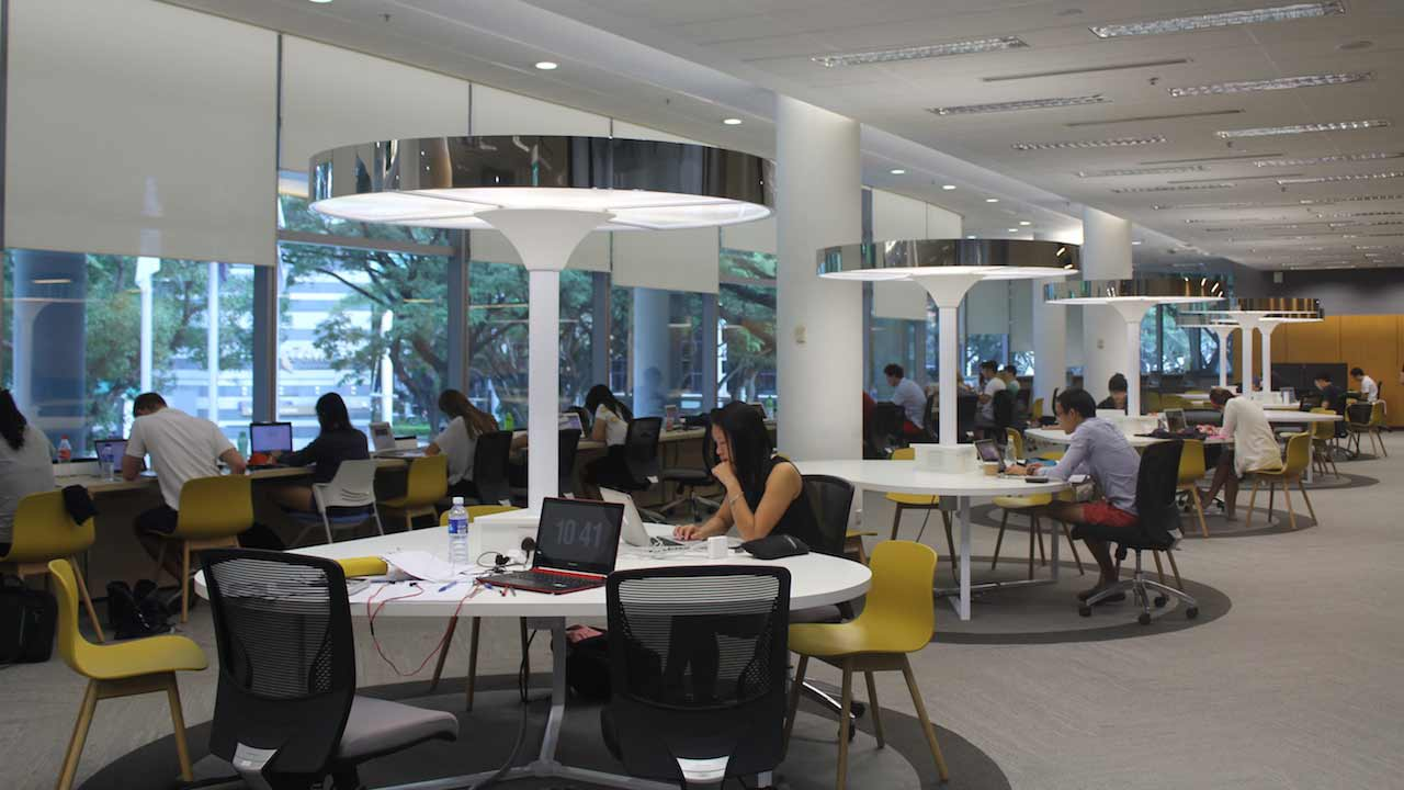 Students sit at round tables in a study room on Singapore Management University's campus