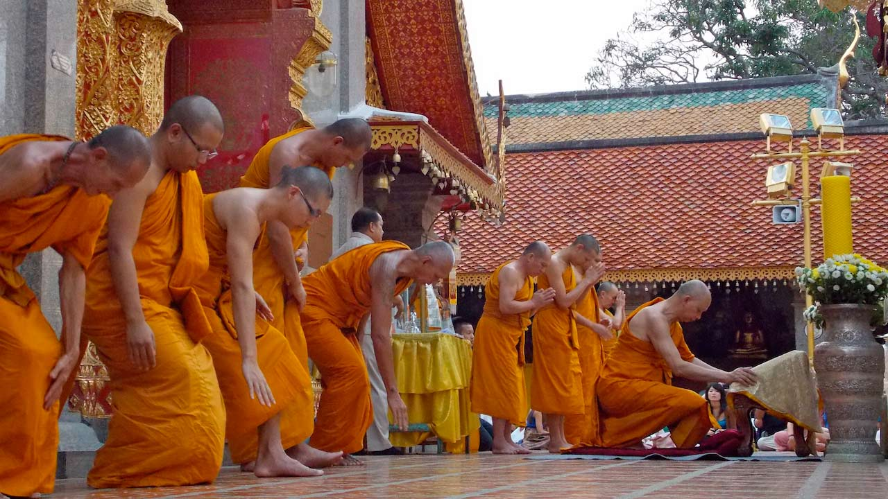 Monks bowing to the Buddha for evening chanting at Wat Doi Suthep in Chiang Mai, Thailand