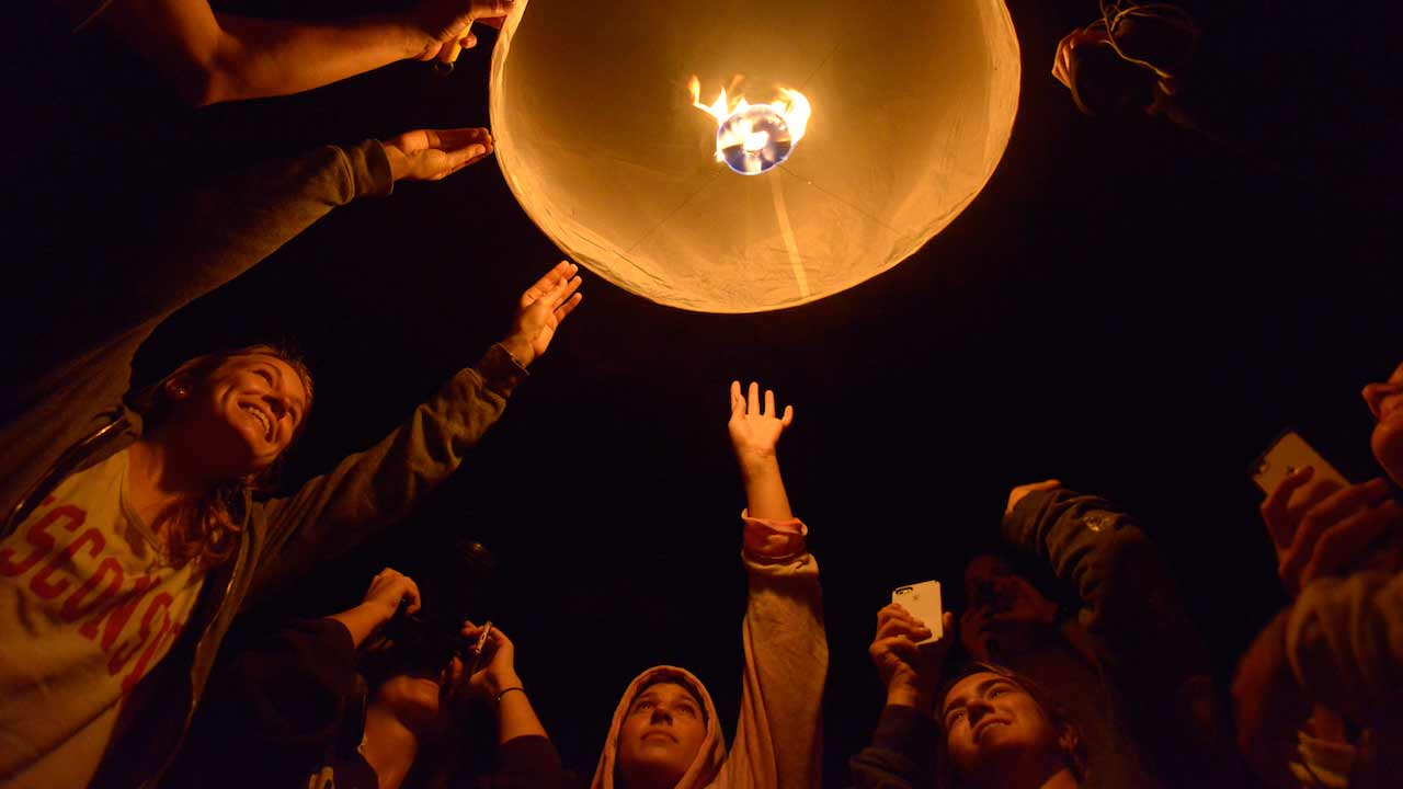 A group of students send a lit lantern into the night sky in Thailand