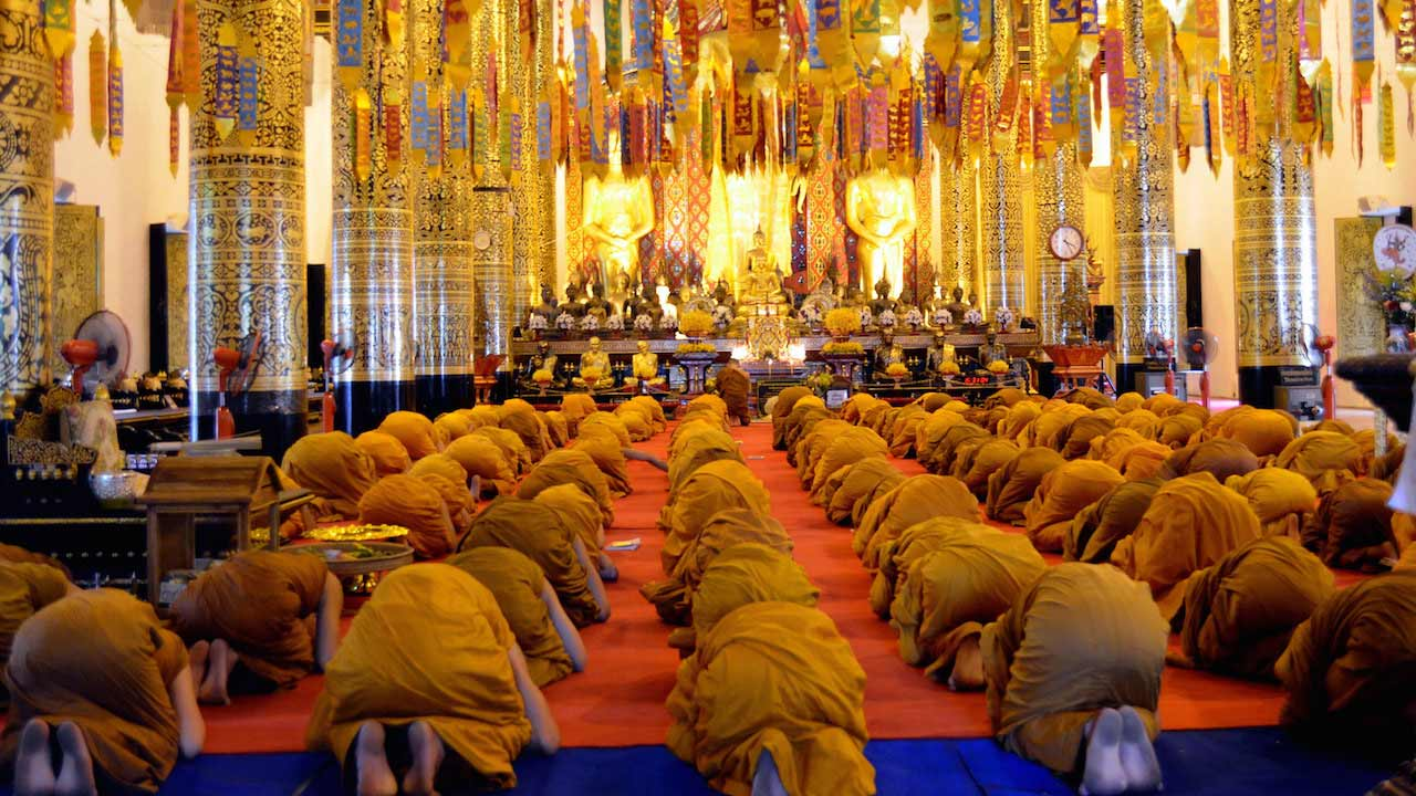 Rows of monks bow to the Buddha at a temple in Chiang Mai, Thailand