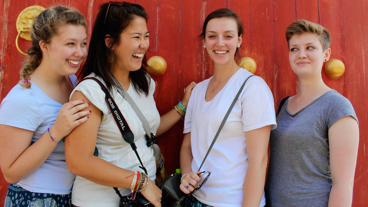 Four female students pose in front of a red and gold door in northern Thailand