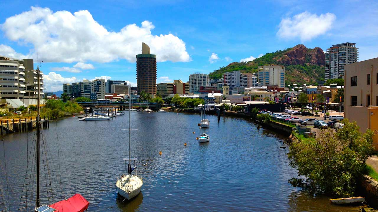 Boats cruise along the canal lined with buildings in Townsville, Australia