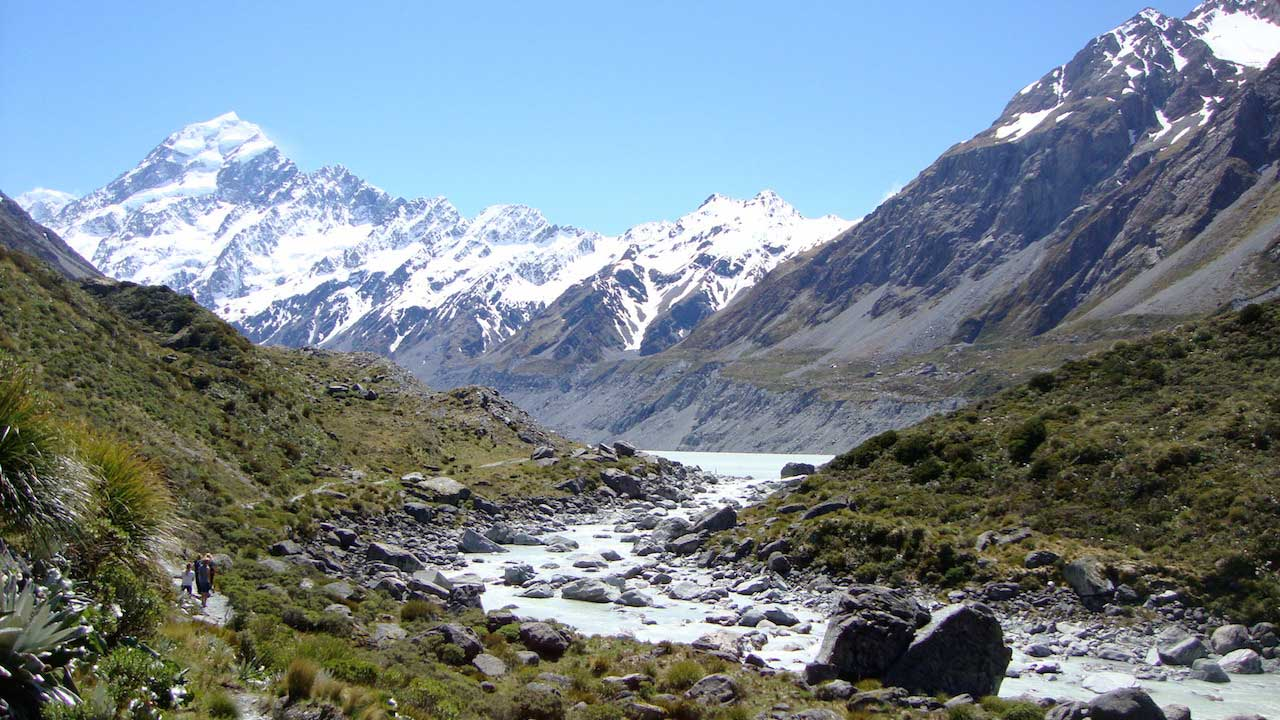 A rocky stream surrounded by grassy peaks leading to snow capped mountains