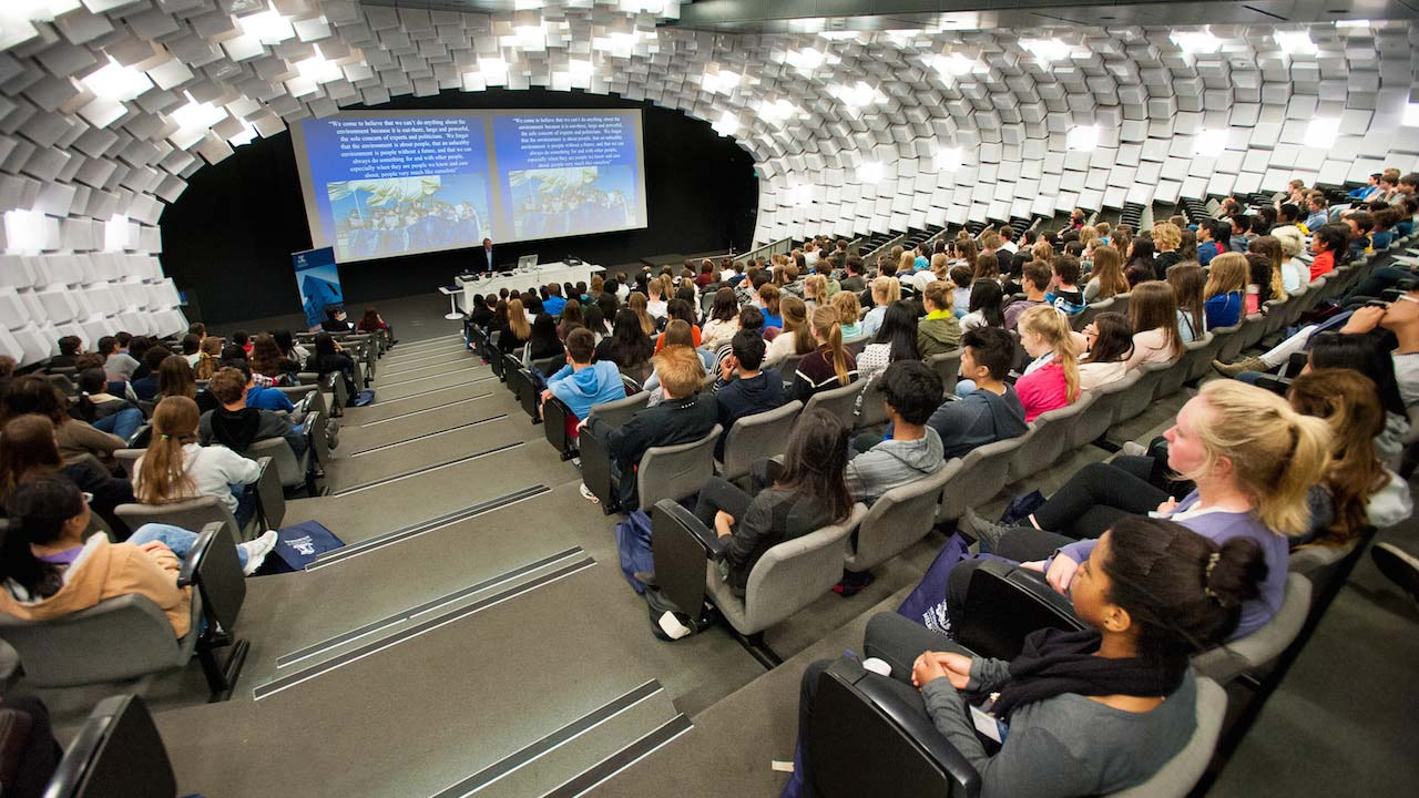 A packed lecture hall with students listening attentively to the professor at University of Melbourne