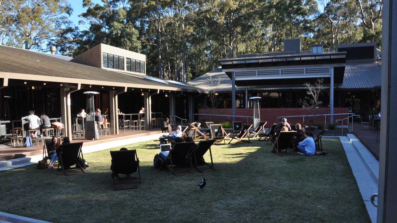 People sit in lawn chairs scattered about the student center's quad on University of Newcastle's campus