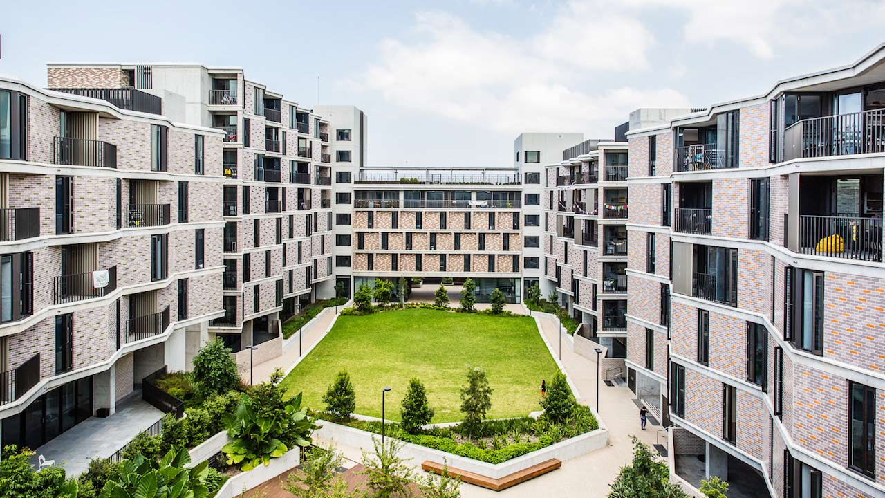 UNSW's modern housing complex, with buildings on three sides and a grass lawn in the middle
