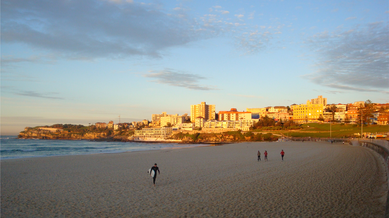 A handful of people walk along the beach as the sun illuminates a nearby neighborhood in Sydney