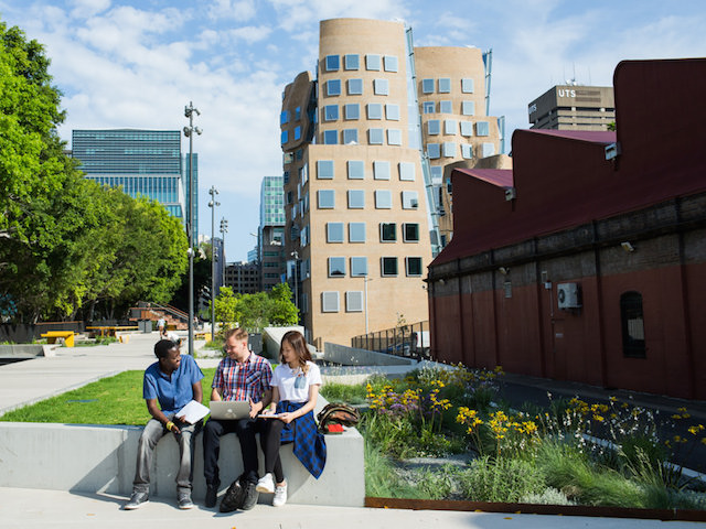 Three people sit on a bench on UTS's campus