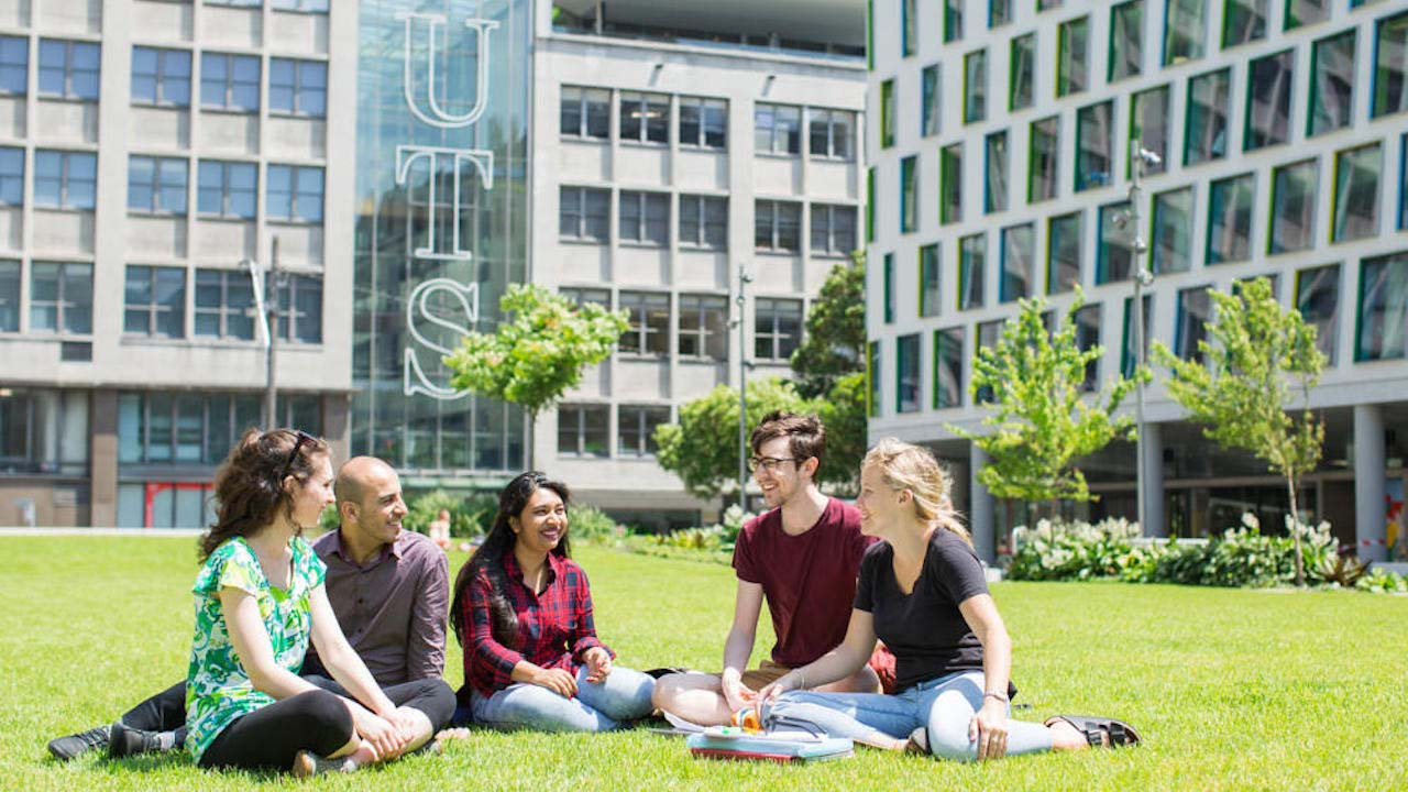 A group of people sit chatting on a grassy quad surrounded by buildings on UTS's campus