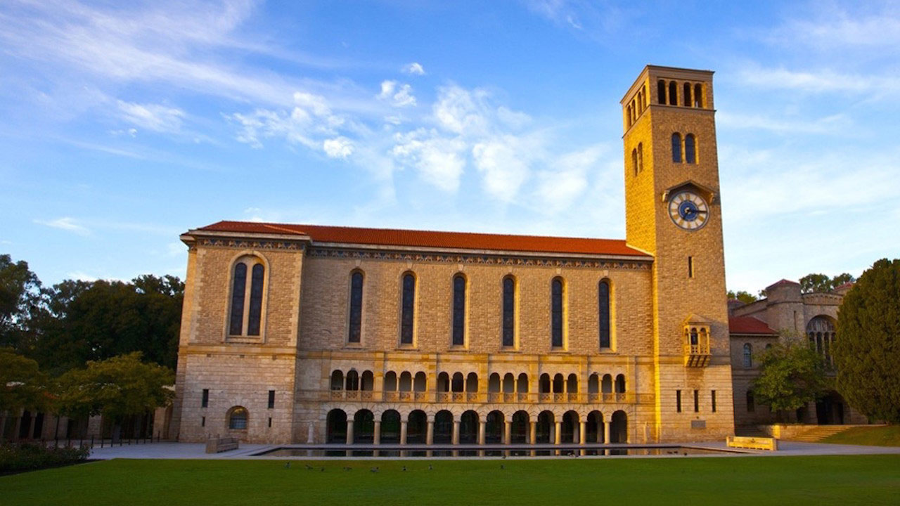 An ornate brick building stands near a grassy quad basking in golden sunlight on University of Western Australia's campus in Perth